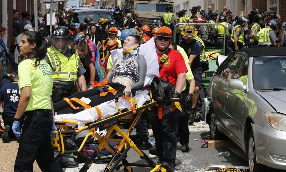 """<span class=""""element-image__caption"""">Rescue personnel help injured people after a car ran into a large group.</span> <span class=""""element-image__credit"""">Photograph: Steve Helber/AP</span>"""