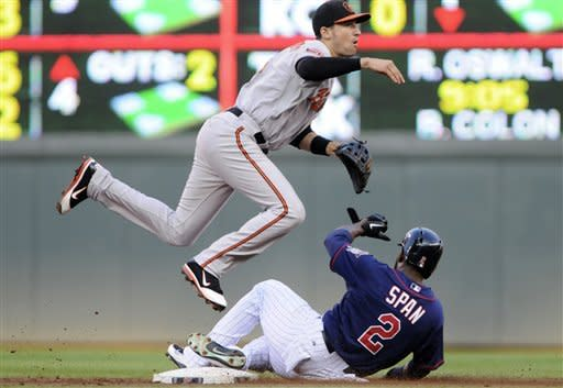 Baltimore Orioles second baseman Ryan Flaherty leaps to complete the double play hit into by Minnesota Twins' Ben Revere after the force at second on Twins' Denard Span in the first inning of a baseball game, Tuesday, July 17, 2012, in Minneapolis. (AP Photo/Jim Mone)