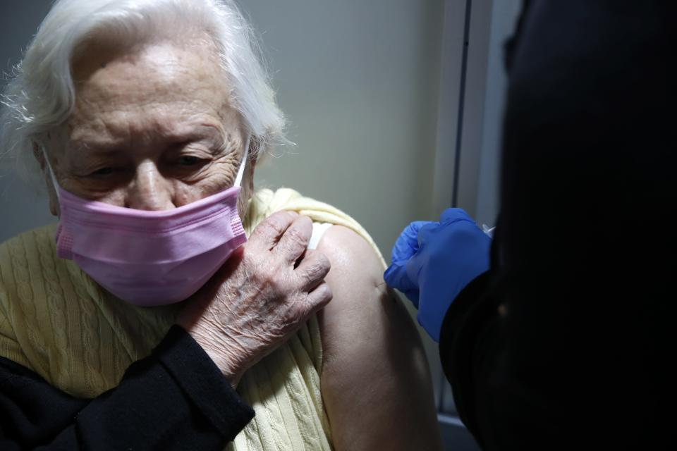 An elderly woman receives the second dose of Moderna COVID-19 vaccine at Promitheas vaccination mega center in Athens, Friday, March 19, 2021. More than 1.35 million doses of the COVID-19 vaccine have been administered so far in Greece, but daily infections remain on the rise despite four months of lockdown measures. (AP Photo/Thanassis Stavrakis)