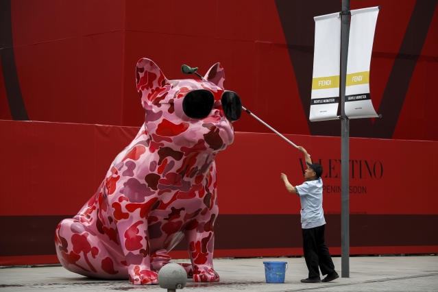 bf1a856c79d2 A worker wipes a dog sculpture outside a luxury fashion boutique under  construction at the capital
