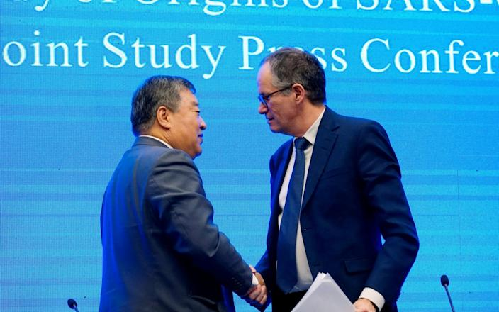 Peter Ben Embarek, a member of the World Health Organization (WHO) team tasked with investigating the origins of the coronavirus disease, shaking hands with Liang Wannian, head of an expert panel on the WHO's Covid response - Aly Song/Reuters