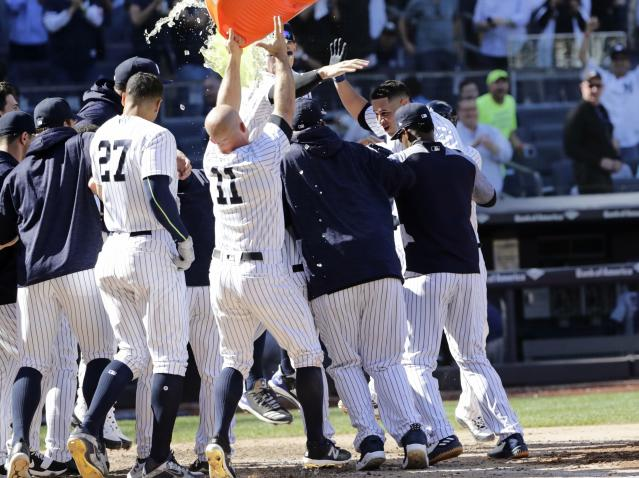 New York Yankees' Gary Sanchez, second from right, celebrates with teammates as he reaches home plate after hitting a three-run home run during the ninth inning of a baseball game against the Minnesota Twins Thursday, April 26, 2018, in New York. The Yankees won 4-3. (AP Photo/Frank Franklin II)