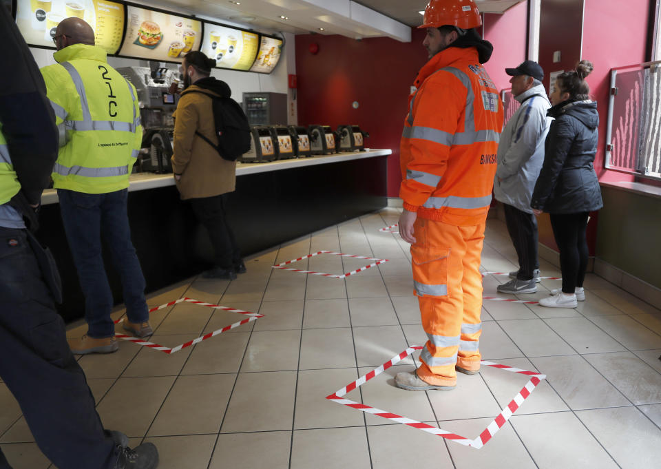 People stand in marked places to keep a social distance at a fast food restaurant in London, Friday, March 20, 2020. For most people, the new coronavirus causes only mild or moderate symptoms, such as fever and cough. For some, especially older adults and people with existing health problems, it can cause more severe illness, including pneumonia. (AP Photo/Frank Augstein)