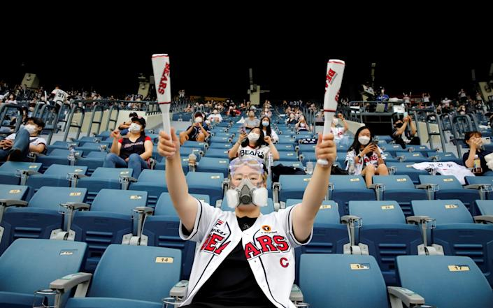 A fan cheers during a KBO baseball game between LG Twins and Doosan Bears at a baseball stadium in Seoul - Reuters