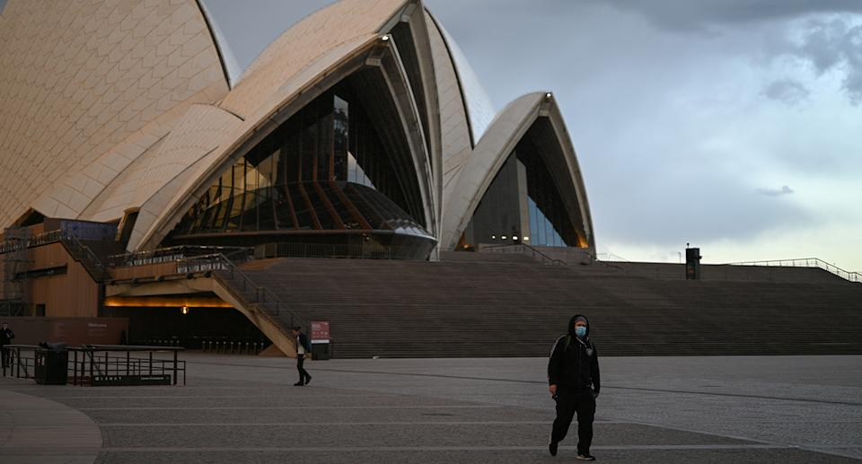 A man wearing a face mask walks in front of the Sydney Opera House as the state of NSW continues to report low numbers for new daily cases of COVID-19 in Sydney, Australia, August 19, 2020. Photo: Reuters