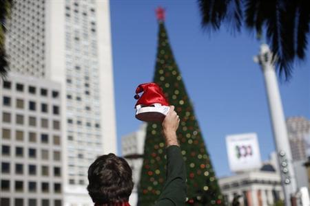 A holiday reveler holds a Santa Claus hat in front of a Christmas tree in Union Square during the annual SantaCon event in San Francisco