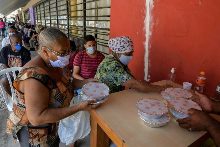 Residents receive meals at a soup kitchen of Paraisopolis, the second-biggest favela in Sao Paulo, with more than 100,000 residents