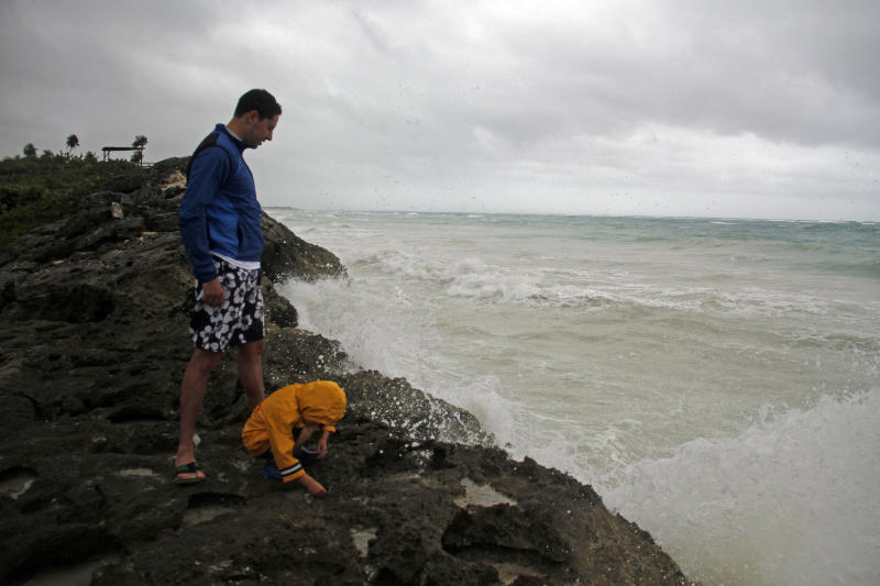 The Valladares family from Mexico City stand near the sea in Tulum, Mexico, Tuesday, Aug. 7, 2012 as Tropical Storm Ernesto brings the threat of hurricane-force winds and torrential rains to the Caribbean coast. The heart of the storm was expected to hit south of Cancun and the Riviera Maya, though strong rain and winds were likely there, and officials prepared shelters there as a precaution. (AP Photo/Israel Leal)