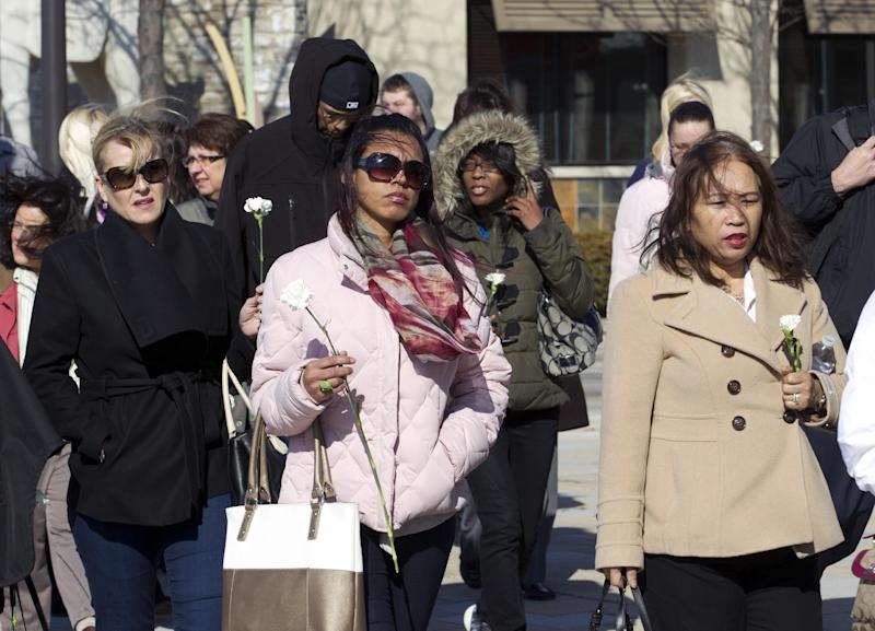 Columbia Mall employees holding carnations walk to the mall which is expected to be open at 1;00 p.m. , on Monday Jan. 27, 2014 in Howard County, Md. Three people died Saturday in a shooting at a mall in suburban Baltimore, including the gunman. ( AP Photo/Jose Luis Magana)