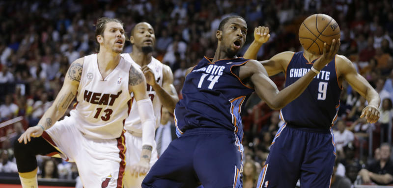 Miami Heat's Mike Miller (13) applies pressure as Charlotte Bobcats' Michael Kidd-Gilchrist (14) rebounds the ball during the first half of a NBA basketball game in Miami, Sunday March 24, 2013. (AP Photo/J Pat Carter)