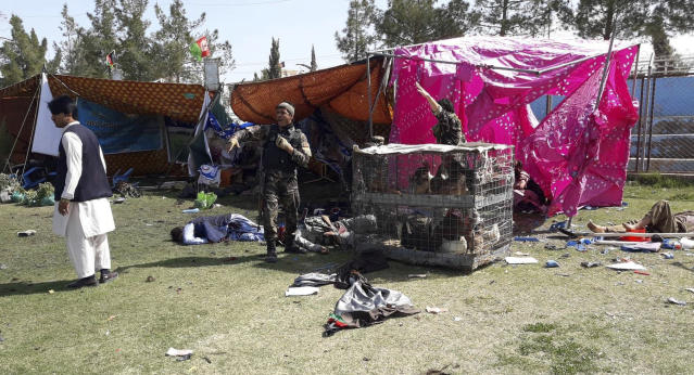 Police and civilians lie on the ground after multiple explosions in Lashkar Gah city of Helmand province, southern Afghanistan, Saturday, Mar. 23, 2019. An Afghan official says that at least three have been killed in twin bomb explosions occurred during the Farmer's Day ceremony in southern Helmand province. (AP Photo/Abdul Khaliq)