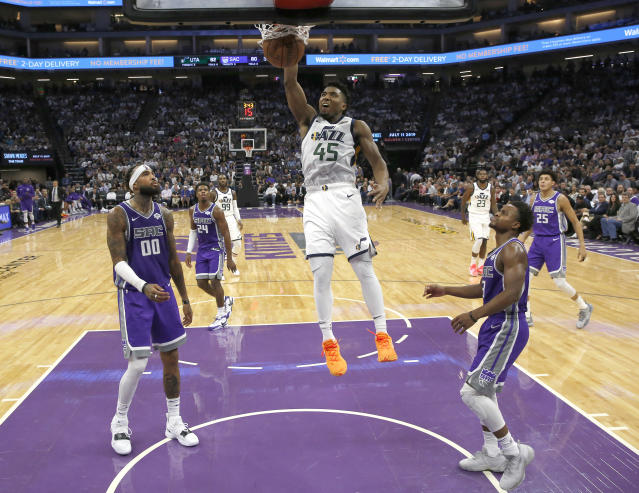 Donovan Mitchell jams it home as Kings Willie Cauley-Stein, left, and Yogi Ferrell look on Wednesday. (AP)