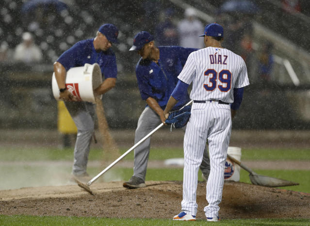 Heavy rain falls as New York Mets relief pitcher Edwin Diaz (39) watches groundskeepers groom the mound with extra dirt during the ninth inning of a baseball game against the St. Louis Cardinals, Thursday, June 13, 2019, in New York. The game, tied at 4-4, was suspended due to the rain. (AP Photo/Kathy Willens)