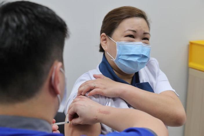 Healthcare worker Sarah Lim receives her coronavirus disease (COVID-19) vaccine at the National Centre for Infectious Diseases (NCID) in Singapore