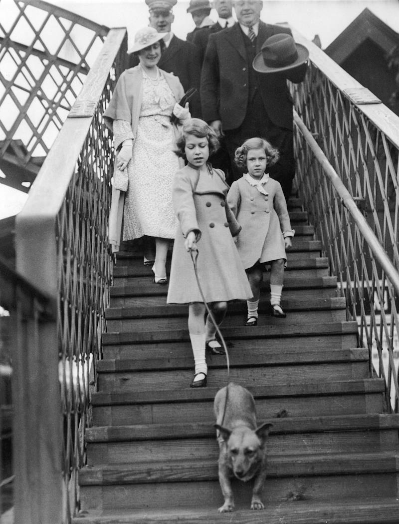 Queen Elizabeth II with the Queen Mother, Princess Margaret, and one of the family's corgis at a railway station, circa 1935.