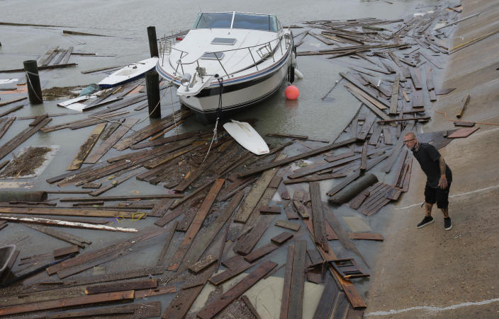 Shawn Pugsley surveys the damage to a private marina after it was hit by Hurricane Hanna, Sunday, July 26, 2020, in Corpus Christi,Texas. Nolan's boat and about 30 others were lost or damaged in the storm. (AP Photo/Eric Gay)