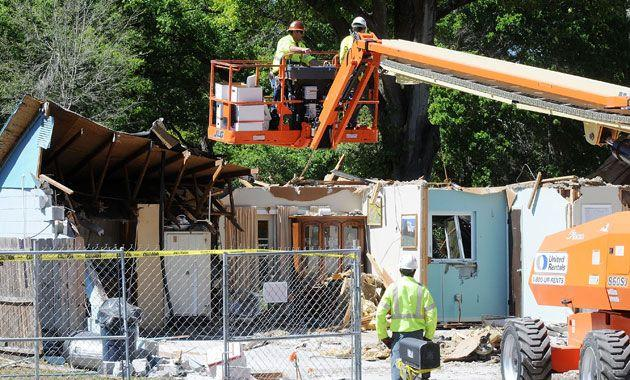 Workers remove belongings from the home where a sinkhole swallowed Jeffrey Bush. Credit: Getty
