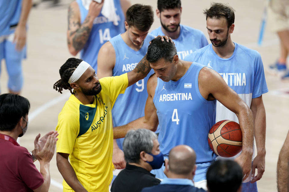 Australia's Patty Mills, left, greets Argentina's Luis Scola (4) after a men's basketball quarterfinal round game at the 2020 Summer Olympics, Tuesday, Aug. 3, 2021, in Saitama, Japan. (AP Photo/Charlie Neibergall)
