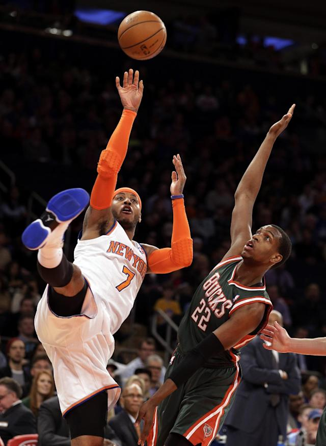 New York Knicks' Carmelo Anthony, left, shoots the ball against Milwaukee Bucks' Khris Middleton in the first quarter of an NBA basketball game at New York's Madison Square Garden, Saturday, March 15, 2014. (AP Photo/Richard Drew)