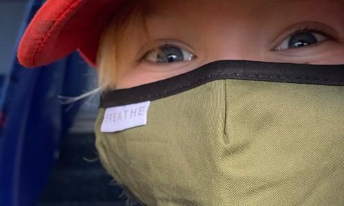 A boy wears a face mask on a bus during the coronavirus crisis