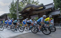 Canada's Michael Woods, foreground right, and other riders round a corner in front of the Okunitama Shrine during the men's cycling road race at the Tokyo Olympics in Tokyo on Saturday, July 24, 2021. (Frank Gunn/The Canadian Press via AP)
