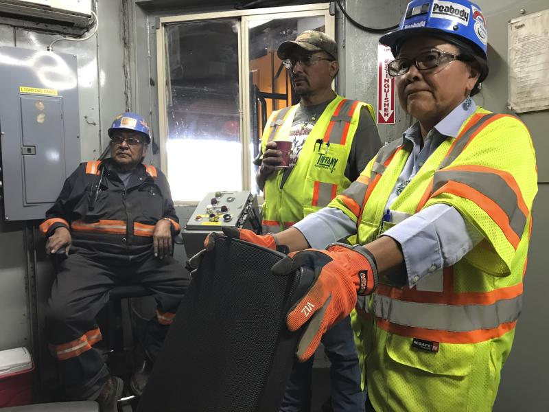 This Aug. 20, 2019, image shows employees with Peabody Energy and the Navajo Generating Station talking about the pending closure of the mine and power plant during a tour of a coal silo near Kayenta, Ariz. The Navajo Generating Station near Page, Arizona, will close before the year ends and other coal-fired plants in the region are on track to shut down or reduce their output in the next few years. (AP Photo/Susan Montoya Bryan)