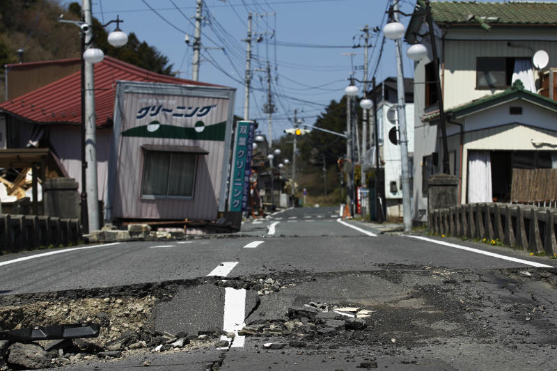 """FILE - This April 17, 2011 file photo shows damage on a street in Futaba, the town where the tsunami crippled Fukushima Dai-ichi nuclear power plant is located, in Fukushima Prefecture, northeastern Japan. After the March 2011 disaster, of all Fukushima communities forced to evacuate, Futaba chose the farthest spot from the nuclear plant - an abandoned high school in Saitama Prefecture, near Tokyo. Atsushi Funahashi, director of """"Nuclear Nation,"""" documented a story of the residents of Futaba in the film. The catastrophe in Japan has set off a flurry of independent films telling the stories of regular people who became overnight victims, stories the creators feel are being ignored by mainstream media and often silenced by the authorities. Nearly two years after the quake and tsunami disaster, the films are an attempt by the creative minds of Japan's movie industry not only to confront the horrors of the worst nuclear disaster since Chernobyl, but also as a legacy and to empower the victims by telling their story for international audiences. (AP Photo/Hiro Komae, File)"""