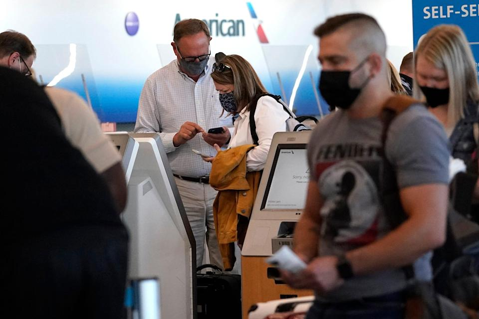 Travelers check in at the American Airlines self-ticket counter at Chicago's O'Hare International Airport on July 2.