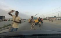 Men carry sticks and block a road in Lagos