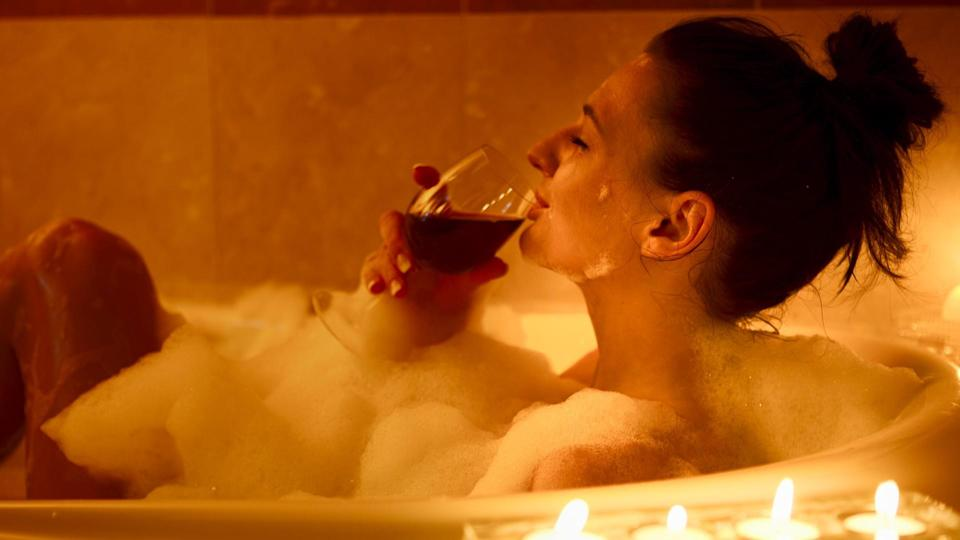 Girl in the bath having a glass of red wine,, candle lit.