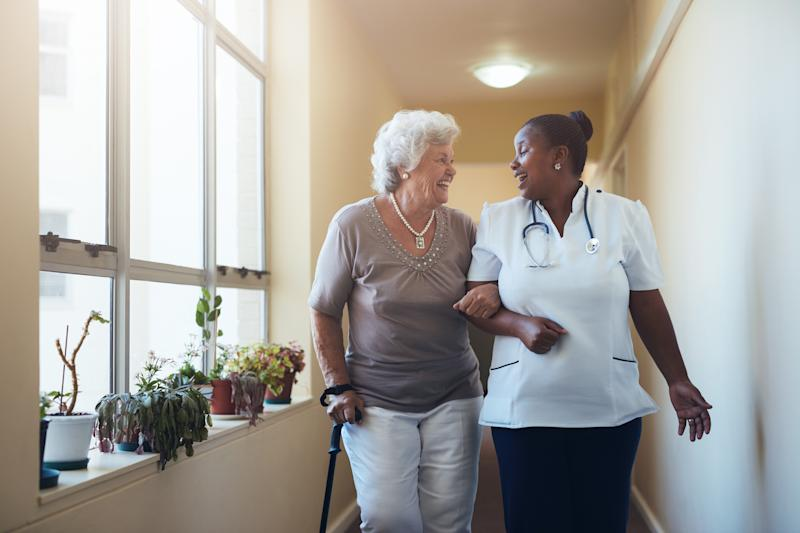 Senior woman with a cane walking and holding the arm of a woman wearing white shirt and stethoscope.