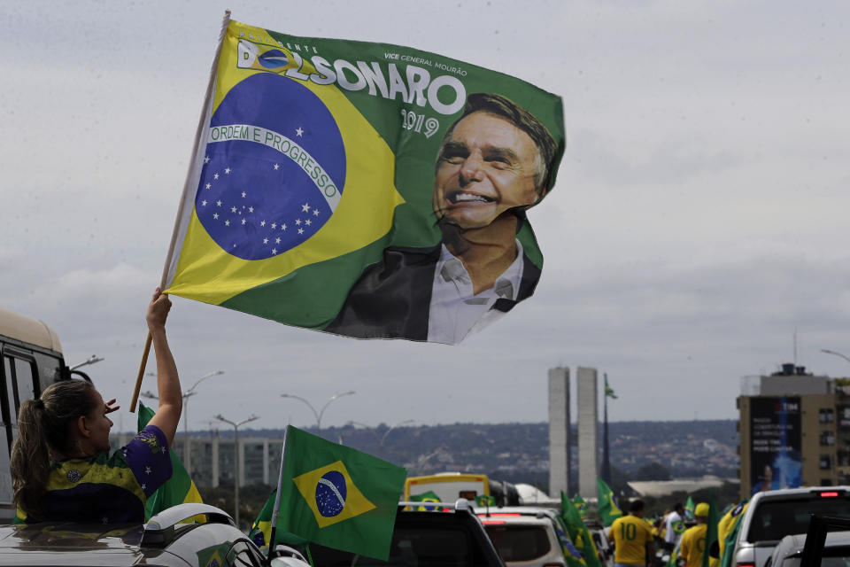 A demonstrator waves a banner with an image of President Jair Bolsonaro, during a caravan backing Bolsonaro's anti-coronavirus-lockdown stance, marking May Day, or International Workers' Day, in Brasilia, Brazil, Saturday, May 1, 2021. (AP Photo/Eraldo Peres)