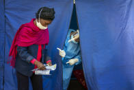 Heath officials check the listings of people who are to be tested for COVID-19 as well as HIV and Tuberculosis, in downtown Johannesburg Thursday, April 30, 2020. Thousands are being tested in an effort to derail the spread of coronavirus. (AP Photo/Jerome Delay)