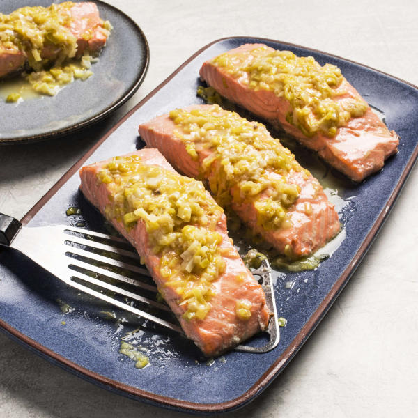 "This undated photo provided by America's Test Kitchen in May 2019 shows Salmon with Leeks and White Wine in Brookline, Mass. This recipe appears in the cookbook ""How to Braise Everything."" (Carl Tremblay/America's Test Kitchen via AP)"