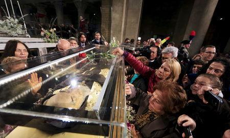 Faithful surround the exhumed body of the mystic saint Padre Pio in a glass, as arrives at the Catholic church of San Lorenzo fuori le Mura in Rome, February 3, 2016. REUTERS/Yara Nardi