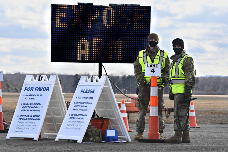 FILE - In this Jan. 18, 2021, file photo, Connecticut National Guard members wait to check-in vehicles for Connecticut's largest COVID-19 Vaccination Drive-Through Clinic in East Hartford, Conn. The push to inoculate Americans against the coronavirus is hitting a roadblock: A number of states are reporting they are running out of vaccine, and tens of thousands of people who managed to get appointments for a first dose are seeing them canceled. (AP Photo/Jessica Hill)