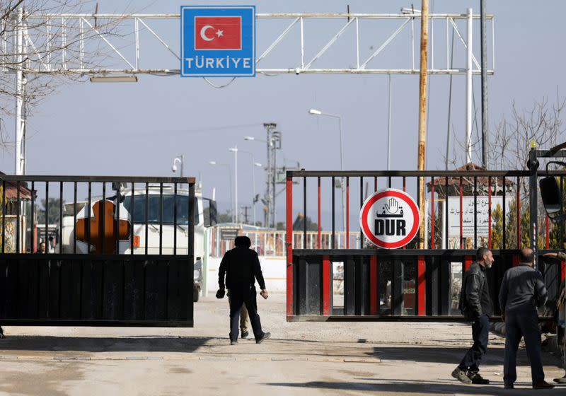 People walk at the Bab el-Salam border crossing between the Syrian town of Azaz and the Turkish town of Kilis