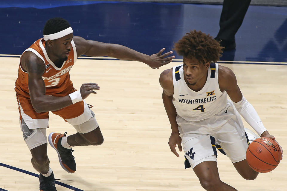 West Virginia guard Miles McBride (4) is defended by Texas guard Courtney Ramey (3) during the first half of an NCAA college basketball game Saturday, Jan. 9, 2021, in Morgantown, W.Va. (AP Photo/Kathleen Batten)