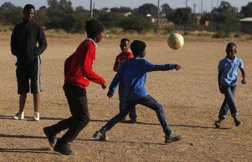 Double amputee and soccer coach Tebogo Mofokeng left, keeps an eye on his players during a friendly soccer match in Winterveldt, South Africa, Sunday, June 17, 2018. Mofokeng's legs were amputated when he was a toddler but that didn't stop him fulfilling his dream of coaching young children. (AP Photo/Denis Farrell)