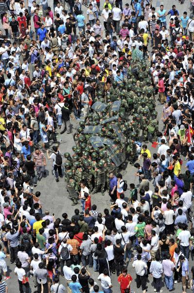 A group of paramilitary policemen are surrounded by anti-Japan protesters outside Shenzhen city's Communist Party headquarters, in southern China's Guangdong province, Sunday, Sept. 16, 2012. Protesters in China continued another day of demonstrations against Japan Sunday, after protests over disputed islands spread across numerous cities and at times turned violent. (AP Photo) CHINA OUT