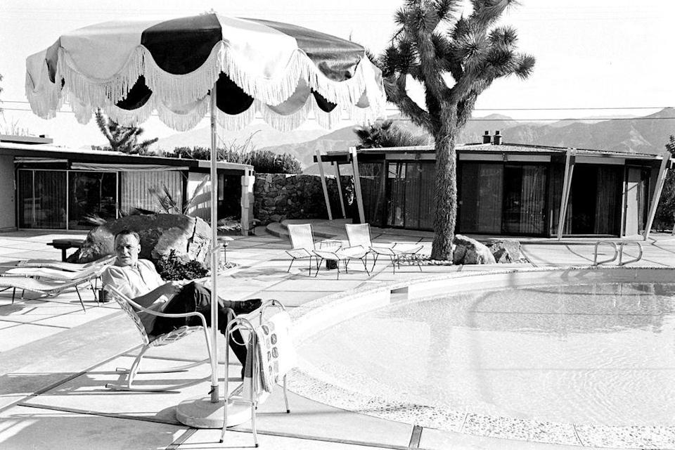 <p>Frank Sinatra reads a script for <em>Marriage on the Rocks </em>under an umbrella at his pool in Palm Springs, California, in 1965. </p>