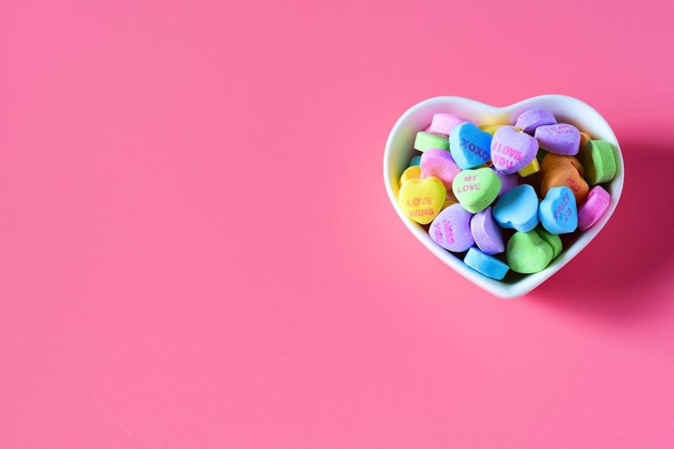 Heart shaped bowl of candy hearts on pink background