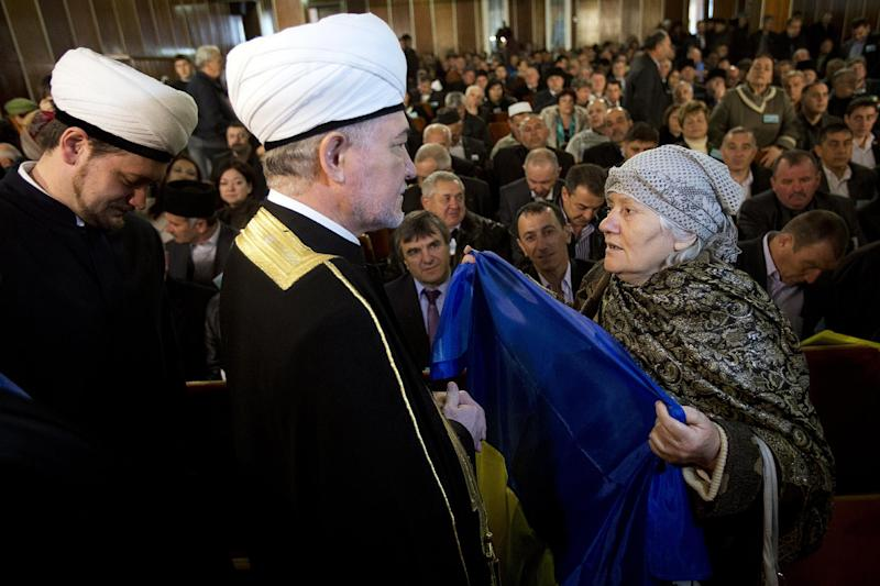 An elderly woman holds a Ukrainian flag in front of Russia's top Muslim Cleric Ravil Gainutdin, center, during the Crimean Tatar Qurultay, a religious congress, in Bakhchysarai, Crimea, Saturday, March 29, 2014. The Crimean Tatar Qurultay, a religious congress will determine whether the Tatars will accept Russian citizenship and the political system that comes with it, or remain Ukrainian citizens on Russian soil. (AP Photo/Pavel Golovkin)
