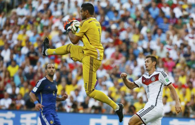 Argentina's goalkeeper Sergio Romero jumps to save the ball in front of teammate Pablo Zabaleta and Germany's Miroslav Klose (R) during their 2014 World Cup final at the Maracana stadium in Rio de Janeiro July 13, 2014. REUTERS/Kai Pfaffenbach (BRAZIL - Tags: SOCCER SPORT WORLD CUP)