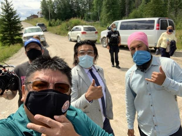 NDP Leader Jagmeet Singh, right, poses for a selfie with NDP MPP Sol Mamakwa, centre, and former Neskantaga chief Chris Moonias, front, during a visit to the First Nation. (Submitted by Chris Moonias - image credit)