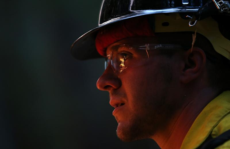 GROVELAND, CA - AUGUST 22: A firefighter from the Colorado based Long Canyon Fire Department monitors a back fire while battling the Rim Fire on August 22, 2013 in Groveland, California. The Rim Fire continues to burn out of control and threatens 2,500 homes outside of Yosemite National Park. Over 1,000 firefighters are battling the blaze that was reduced to only 2 percent containment after it nearly tripled in size overnight. (Photo by Justin Sullivan/Getty Images)