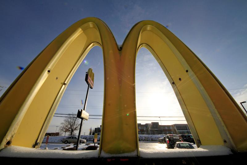 """FILE - This Jan. 21, 2014 file photo, cars drive past the McDonald's Golden Arches logo at a McDonald's restaurant in Robinson Township, Pa. McDonald's says it will switch to cage-free eggs in the U.S. and Canada over the next decade, marking the latest push under CEO Steve Easterbrook to try and reinvent the Big Mac maker as a """"modern, progressive burger company."""" (AP Photo/Gene J. Puskar, File)"""