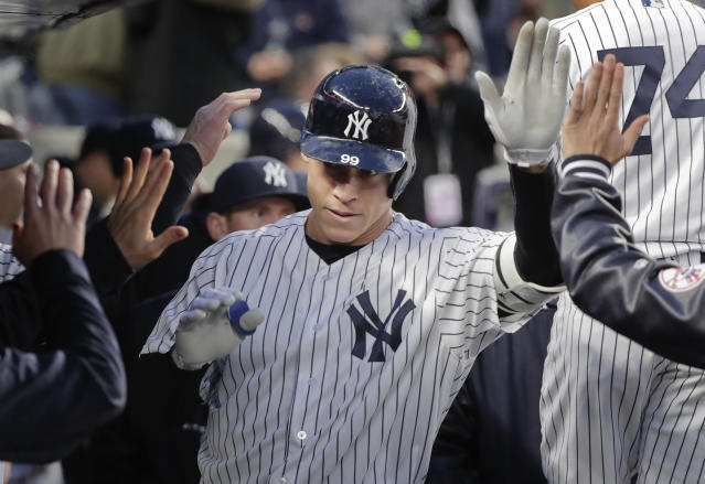 New York Yankees Aaron Judge is congratulated by teammates in the dugout after hitting a solo home run against the Miami Marlins during the second inning of a baseball game, Monday, April 16, 2018, in New York. (AP Photo/Julie Jacobson)