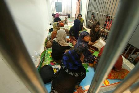 FILE PHOTO: Rohingya people are seen detained in a police station after a fishing boat carrying more than sixty Rohingya refugees was found beached at Rawi island