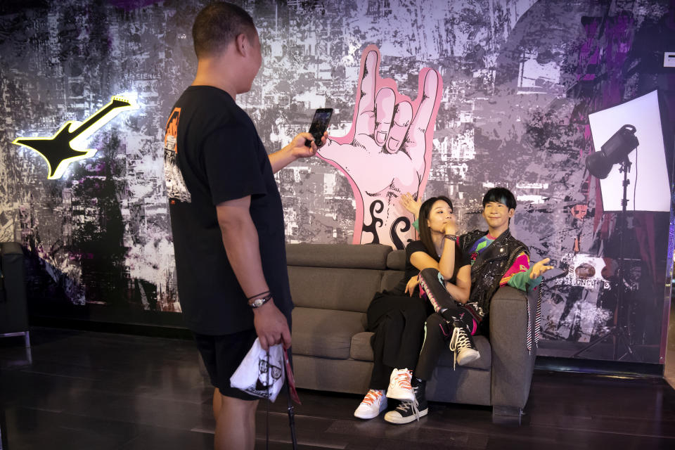 A visitor poses for a photo with a figure of Chinese singer Wowkie Zhang at Madame Tussaud's in Beijing, Tuesday, Aug. 31, 2021. China's rulers are targeting hugely popular online games and celebrity culture with a raft of new restrictions, meant to promote its vision for a powerful, more wholesome society. The message? Play less, study and work more. (AP Photo/Mark Schiefelbein)